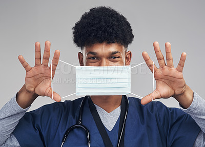 Buy stock photo Shot of a male nurse holding up a surgical mask while standing against a grey background