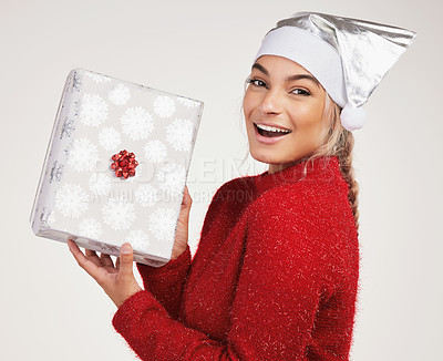 Buy stock photo Studio shot of a young woman holding a gift box against a grey background