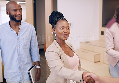 Buy stock photo Shot of an attractive young businesswoman standing and shaking hands with a colleague in the office