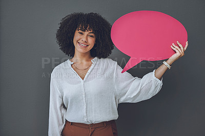 Buy stock photo Studio portrait of a young woman holding a pink speech bubble against a grey background