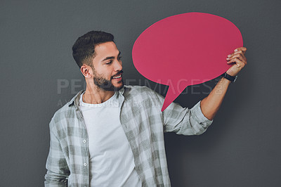 Buy stock photo Studio shot of a young man holding a pink speech bubble against a grey background