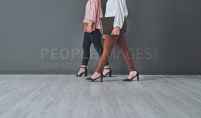 Buy stock photo Studio shot of two unrecognisable woman walking against a grey background