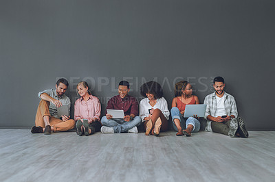 Buy stock photo Studio shot of a diverse group of people using digital devices against a grey background