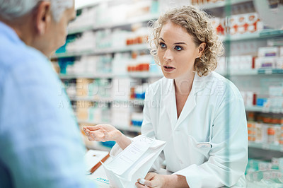 Buy stock photo Cropped shot of an attractive young chemist helping a senior male customer in her pharmacy