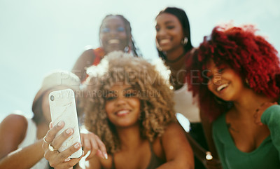 Buy stock photo Shot of a group of young girl friends using a phone in the city