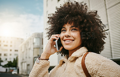 Buy stock photo Shot of a beautiful young woman talking on her cellphone while out in the city