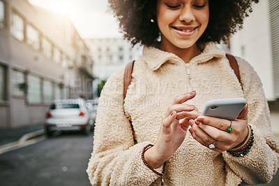 Buy stock photo Shot of a beautiful young woman using her cellphone while out in the city