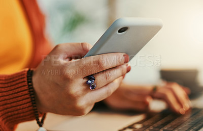 Buy stock photo Shot of a businesswoman using her smartphone while working from a coffee shop
