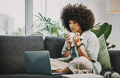 Buy stock photo Shot of an attractive young woman sitting alone on her sofa at home and using her laptop while drinking coffee