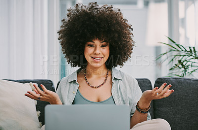 Buy stock photo Shot of an attractive young woman sitting on her sofa at home and using her laptop for a video call