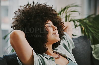 Buy stock photo Shot of an attractive young woman sitting alone on her sofa with her hands behind her head and feeling relaxed
