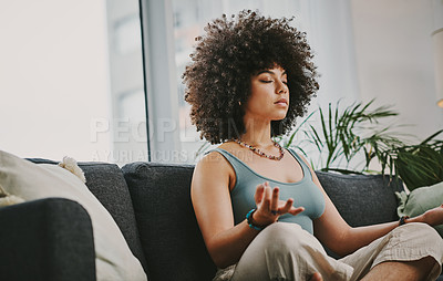 Buy stock photo Shot of an attractive young woman sitting alone on her sofa at home and meditating