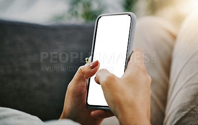 Buy stock photo Cropped shot of an unrecognisable woman lying down on her sofa at home and using her cellphone