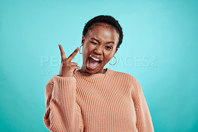 Buy stock photo Shot of a beautiful young woman showing the peace sign while standing against a turquoise background