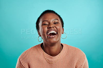 Buy stock photo Shot of a young woman laughing while standing against a turquoise background