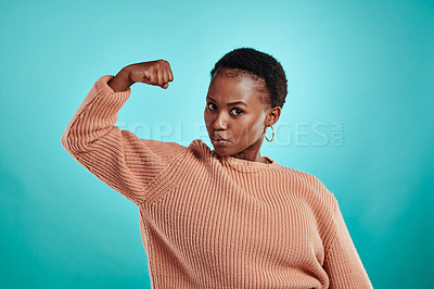 Buy stock photo Shot of a beautiful young woman flexing while standing against a turquoise background