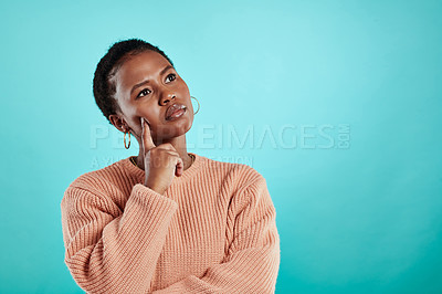 Buy stock photo Shot of a young woman looking thoughtful while standing against a turquoise background