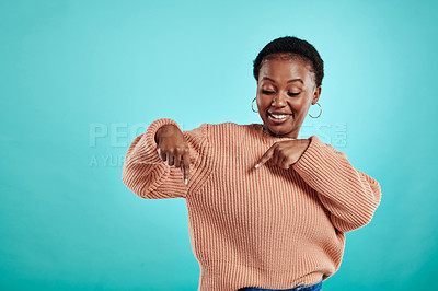 Buy stock photo Shot of a young woman pointing down while standing against a turquoise background