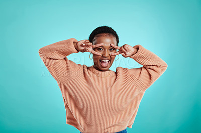 Buy stock photo Shot of a young woman gesturing a v-sign over her eyes