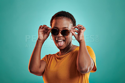 Buy stock photo Shot of a young woman wearing sunglasses while standing against a turquoise background