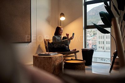 Buy stock photo Shot of a young woman using her smartphone to make a video call