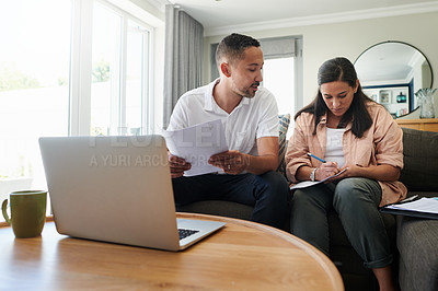 Buy stock photo Shot of a young couple sitting on the sofa at home together and using their laptop to calculate their finances