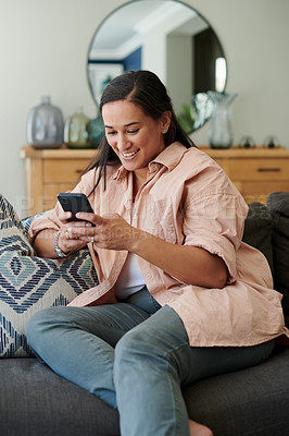 Buy stock photo Shot of a young woman sitting alone on her sofa at home and using her cellphone to work from home