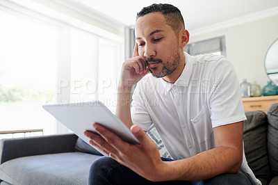 Buy stock photo Shot of a young man sitting alone on his sofa at home and looking contemplative while using a digital tablet