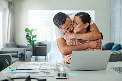 Buy stock photo Shot of a young man hugging and kissing his wife while she uses her laptop to work from home