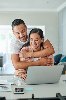 Buy stock photo Shot of a young man hugging his wife while she uses her laptop to work from home