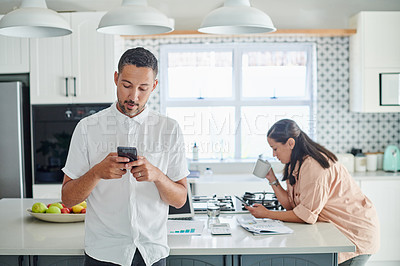 Buy stock photo Shot of a young couple standing in the kitchen at home and using their cellphones