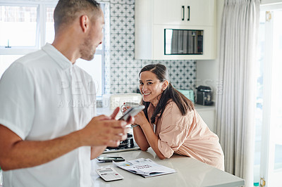 Buy stock photo Shot of an attractive young woman enjoying a cup of coffee in her kitchen while her husband uses his cellphone