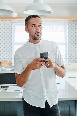 Buy stock photo Shot of a handsome young man standing alone in his kitchen and looking contemplative while using his cellphone