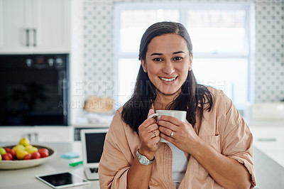 Buy stock photo Shot of an attractive young woman standing alone in her kitchen and enjoying a cup of coffee