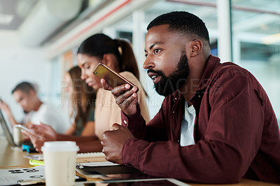 Buy stock photo Cropped shot of a handsome young businessman sending a voice message while sitting in the boardroom with his colleagues