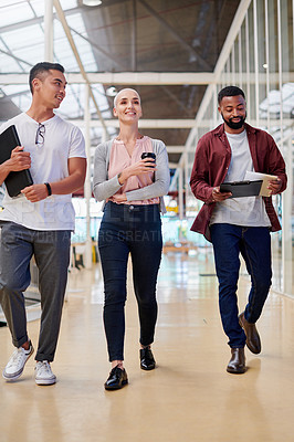 Buy stock photo Full length shot of a group of young businesspeople walking through the corridor of their creative office