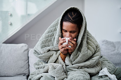 Buy stock photo Shot of a young man with the flu sitting on the couch at home