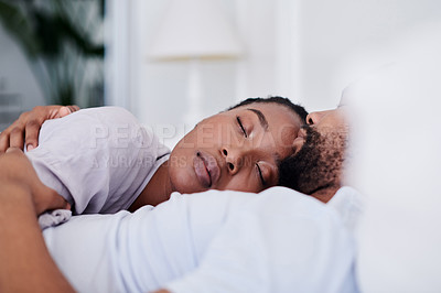 Buy stock photo Shot of a young couple cuddling while sleeping in bed together at home