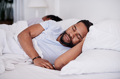 Buy stock photo Shot of a handsome young man sleeping in his bed at home while his girlfriend lies behind him