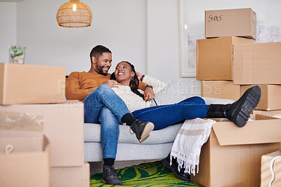 Buy stock photo Shot of a young couple sitting on the couch in their new home