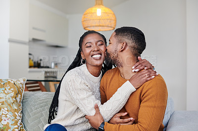 Buy stock photo Shot of a young man kissing his girlfriend on the cheek while relaxing together at home