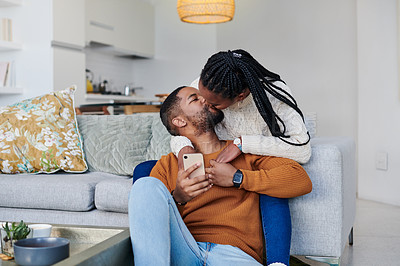 Buy stock photo Shot of an affectionate young couple kissing each other while relaxing together at home