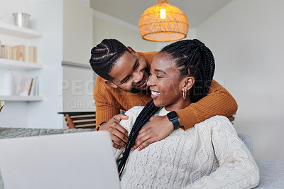 Buy stock photo Shot of a young couple using a laptop while relaxing together at home