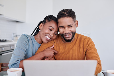 Buy stock photo Shot of a young couple being affectionate and using a laptop while having coffee together at home