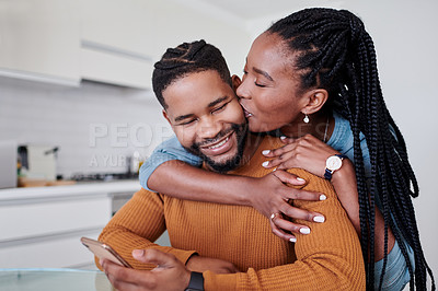 Buy stock photo Shot of a young couple being affectionate in the kitchen together at home