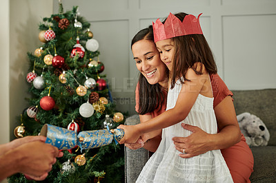 Buy stock photo Cropped shot of an affectionate young family popping Christmas crackers in their living room at home