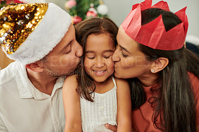 Buy stock photo Cropped shot of an adorable little girl being kissed on each cheek by her mother and father at home on Christmas eve