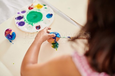 Buy stock photo Cropped shot of a unrecognizable girl painting eggs at home