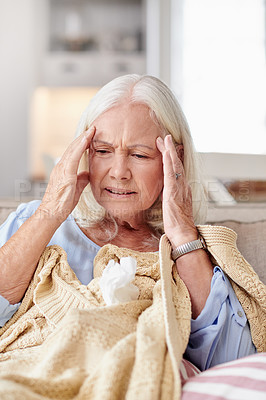 Buy stock photo Shot of a senior woman experiencing a headache while feeling sick at home
