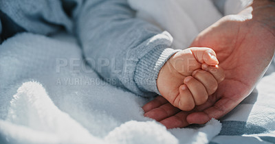 Buy stock photo Shot of an unrecognisable woman holding her baby's hand on the bed at home